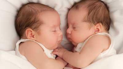 Dua bayi kembar berhadapan satu sama lain