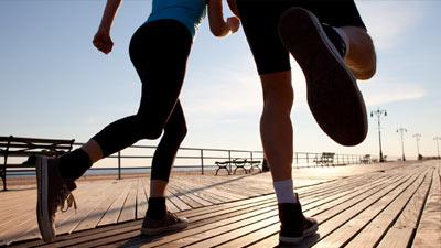 Dua orang yang sedang jogging dengan fokus pada langkah kaki