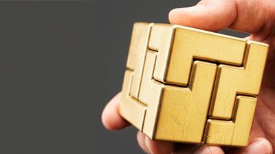 kubus emas terbuat dari puzzle sedang dipegang