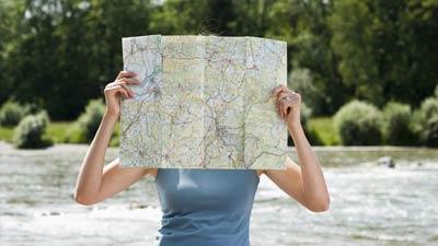 Wanita sedang berusaha membaca peta di samping sungai