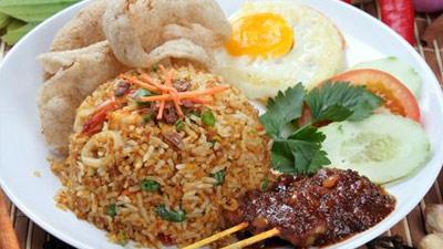 Nasi goreng gaya Indonesia disajikan dengan kerupuk, telor, dan sate
