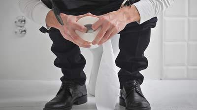 Pria sedang buang air besar sambil pegang tissue toilet