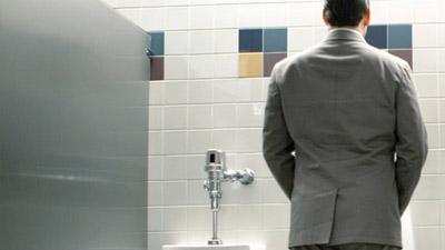 Pria sedang buang air kecil di urinal